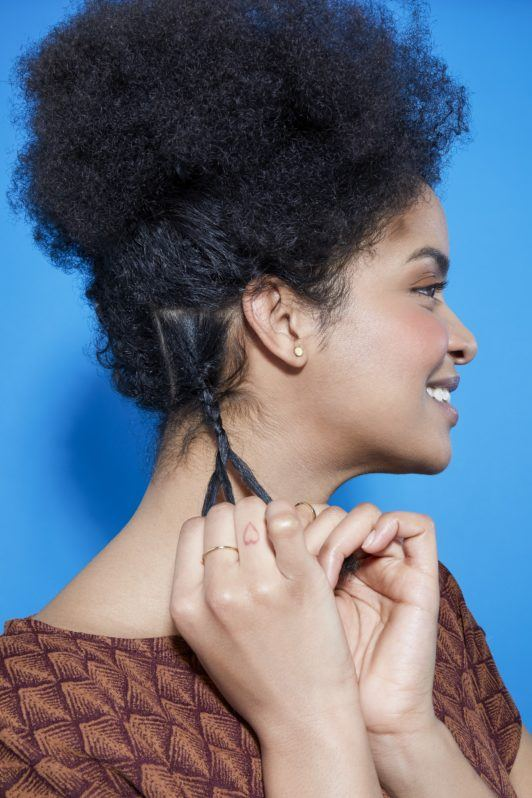 side view of a woman with natural curly hair braiding a small section of hair