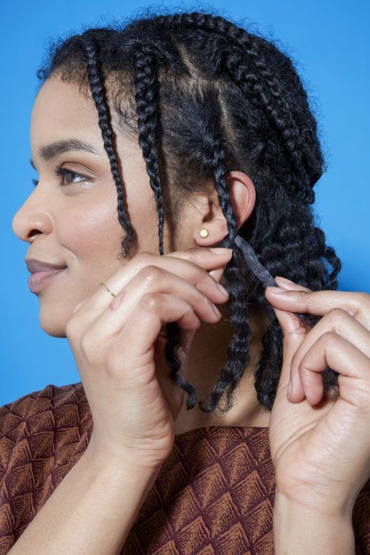 side view of a woman with natural curly hair braiding her hair in small sections