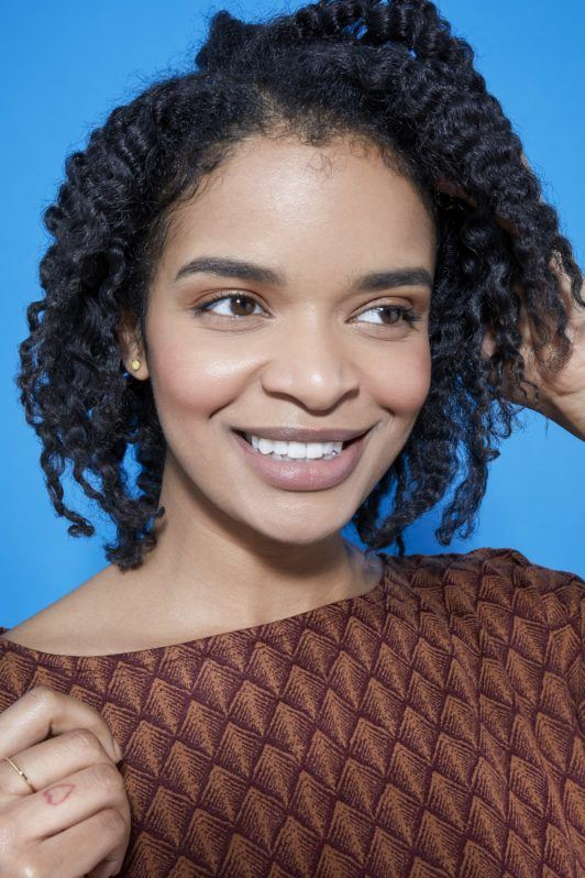 woman with natural curly hair in a bob length cut touching her hair
