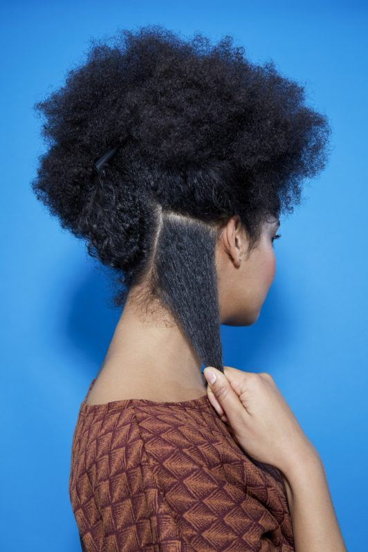 back view of a woman with natural hair separating it into sections ready for braiding