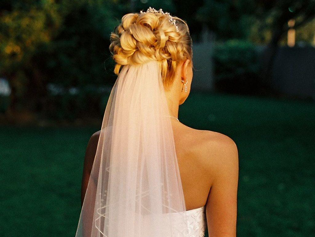 blonde bridal model with her hair in an intricate updo with a veil