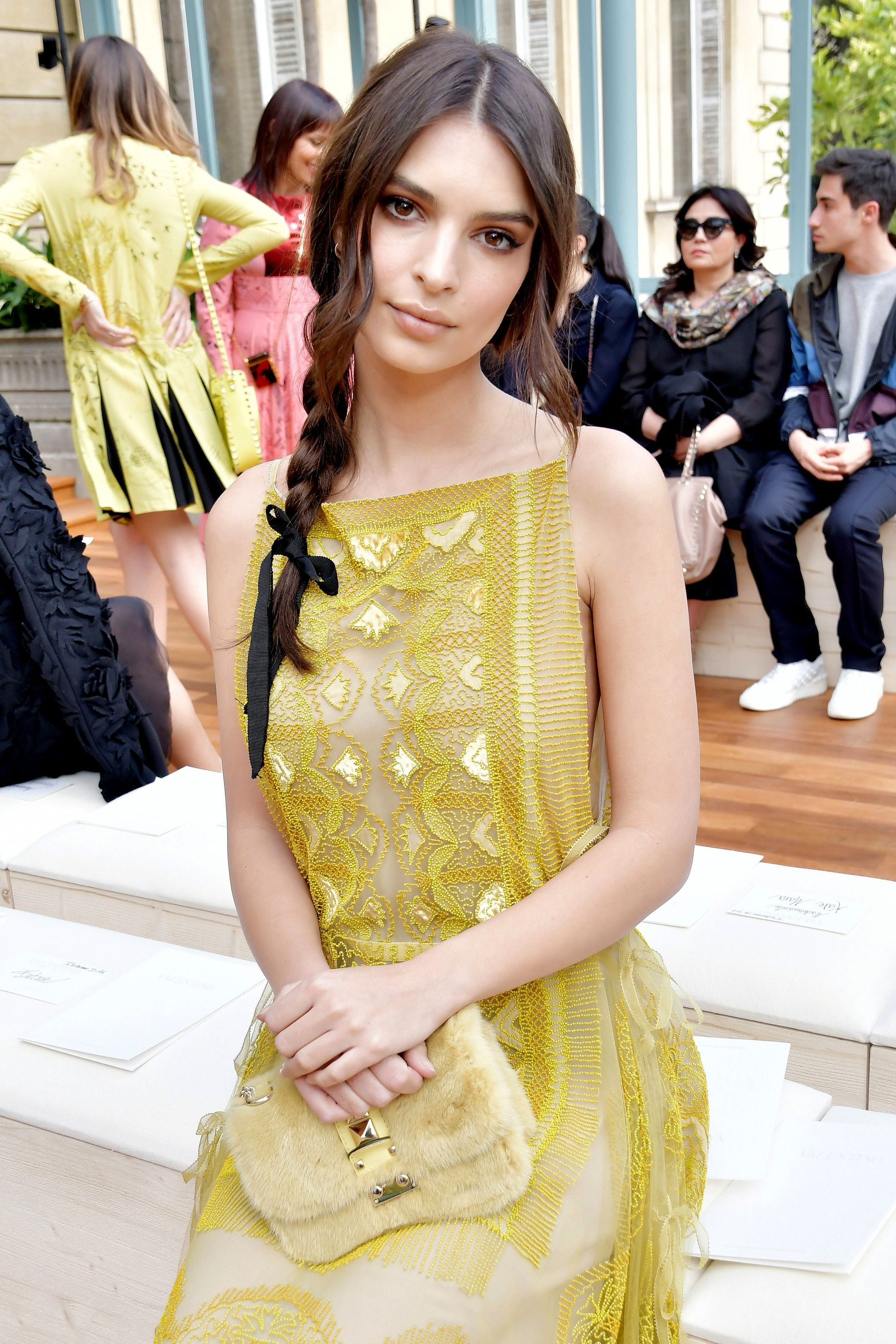 emily ratajkowski wearing a citrus coloured lace dress with her long brunette hair in a side braid with black bow