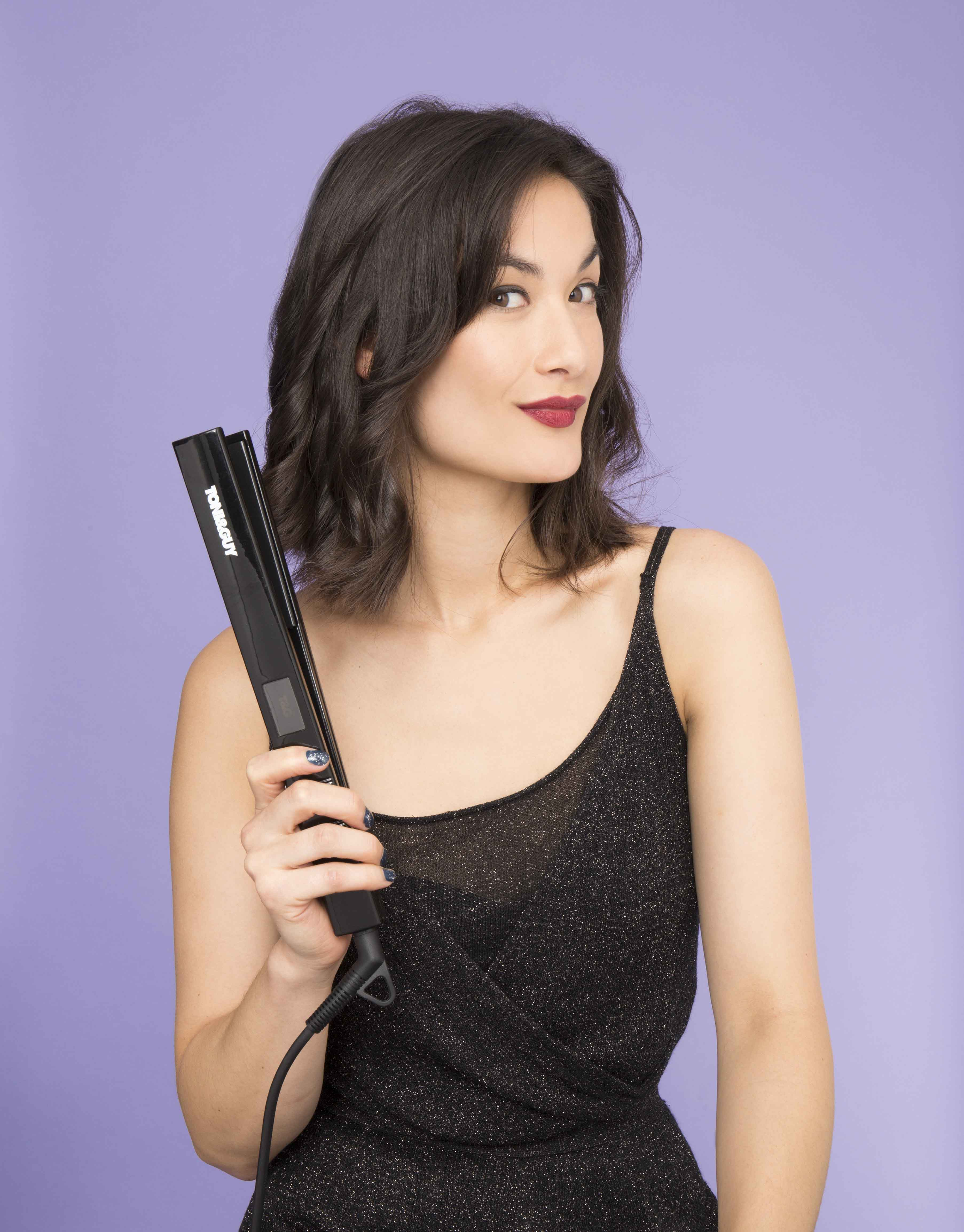 How to curl your short hair with a straightener: Young Asian woman with short black hair holding a straightener