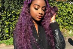 justine sky with long purple curly hair outside