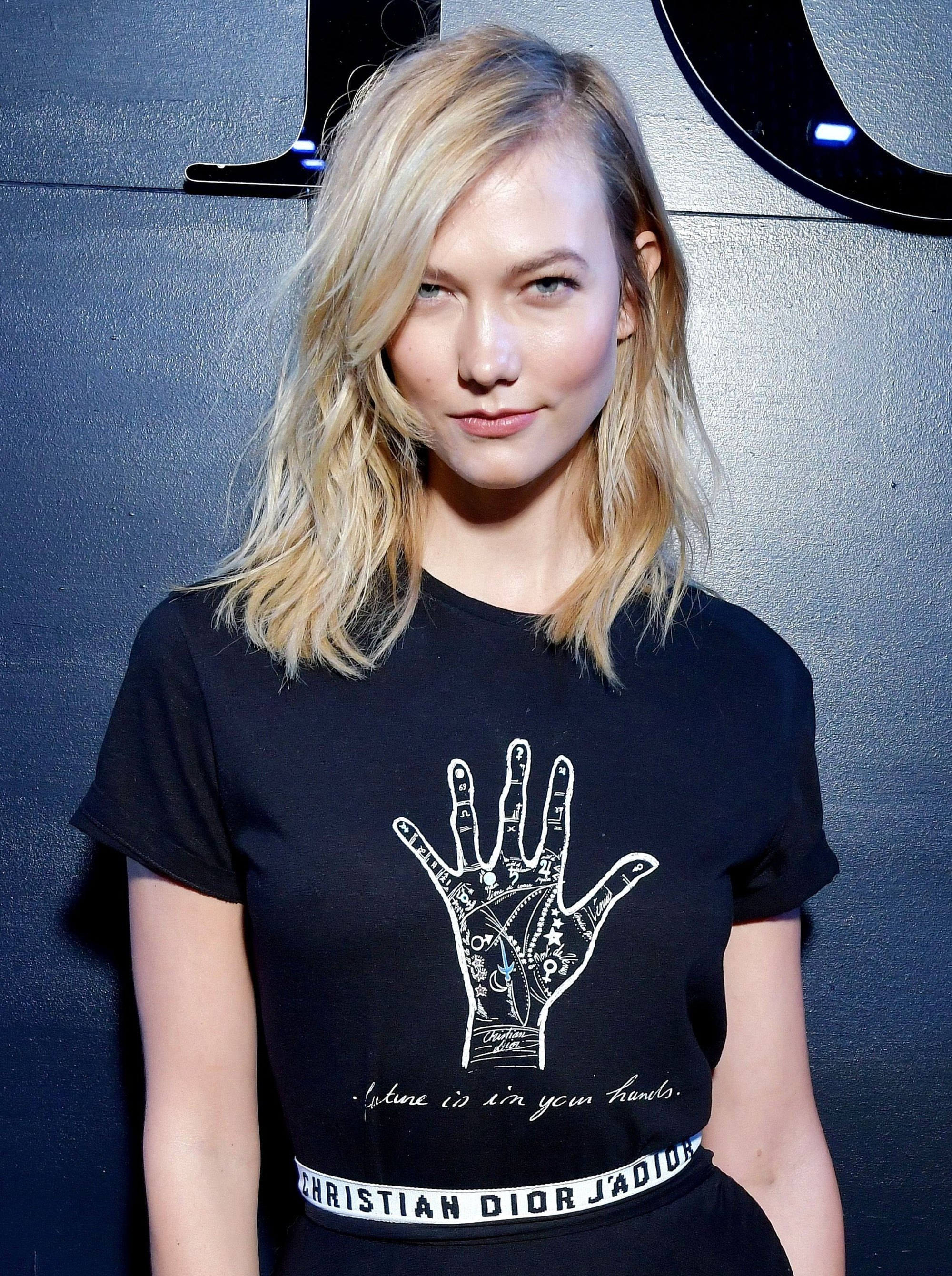 karlie kloss wearing a black tshirt with hand print with blonde shoulder length layered mom hair