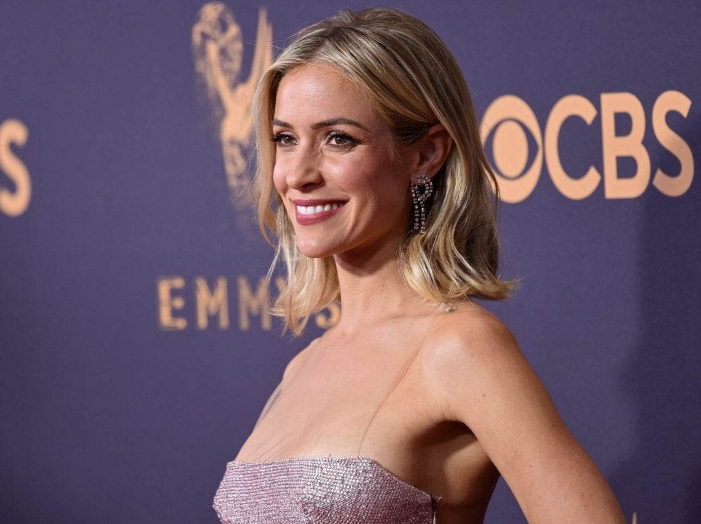 90s hairstyles: image of Kristin Cavallari on the red carpet with wavy blonde shoulder length hair, evening dress and drop earrings