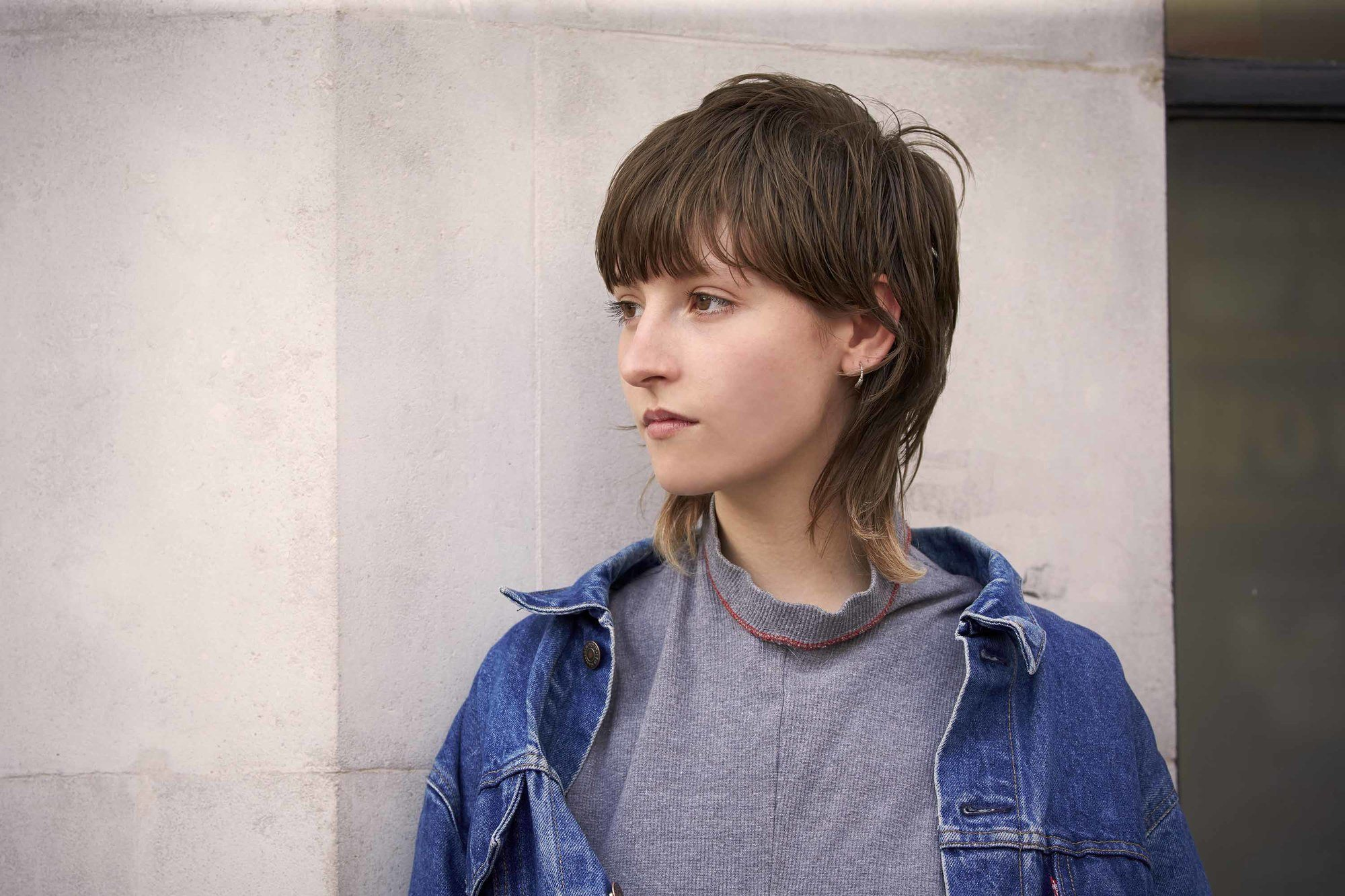model with funky short hair in a mullet style, wearing denim