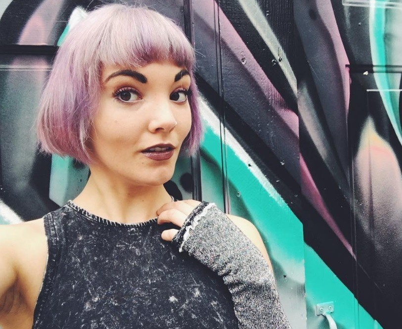Woman wearing grey top with lilac short French bob hair