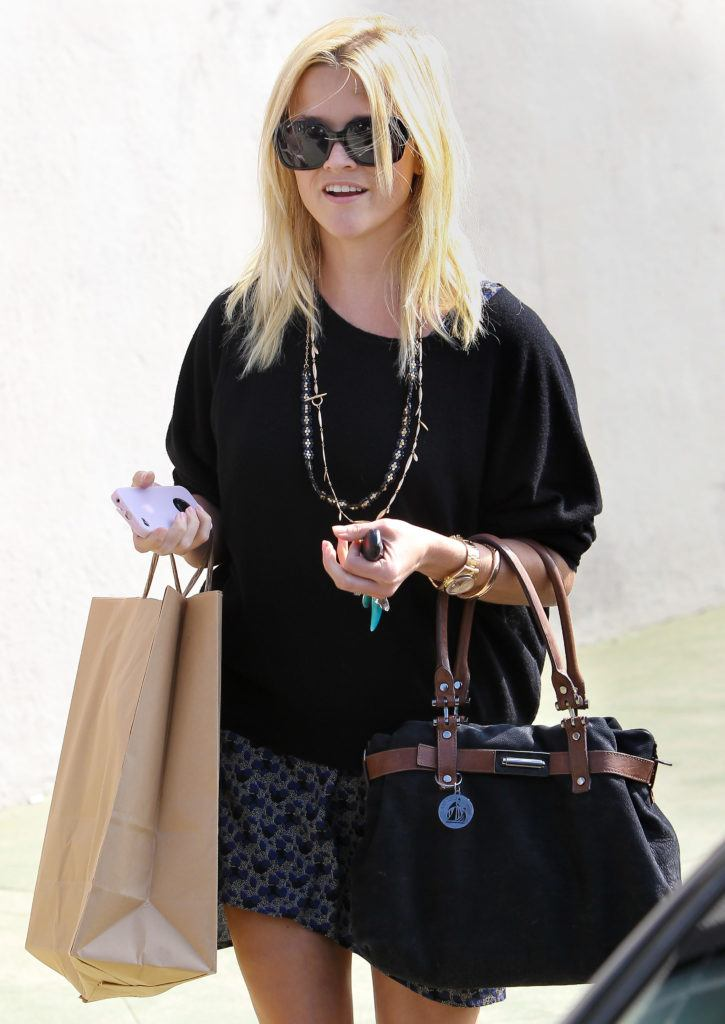 90s hairstyles: Reese Witherspoon out and about in Los Angeles with blonde shoulder to medium length mom hair and sunglasses carrying shopping bags