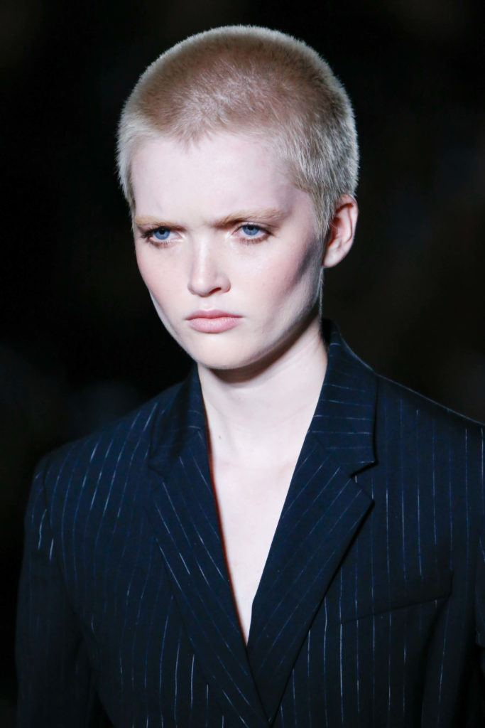 fashion short hairstyles: model with a platinum blonde buzzcut on the runway