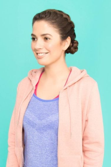 Sporty looking brunette with braided bun wearing a pink hoodie
