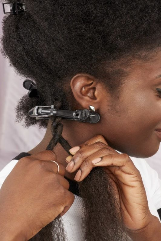 How to do marley braid hair: Woman twisting her marley hair around her hair in the All Things Hair UK Studio