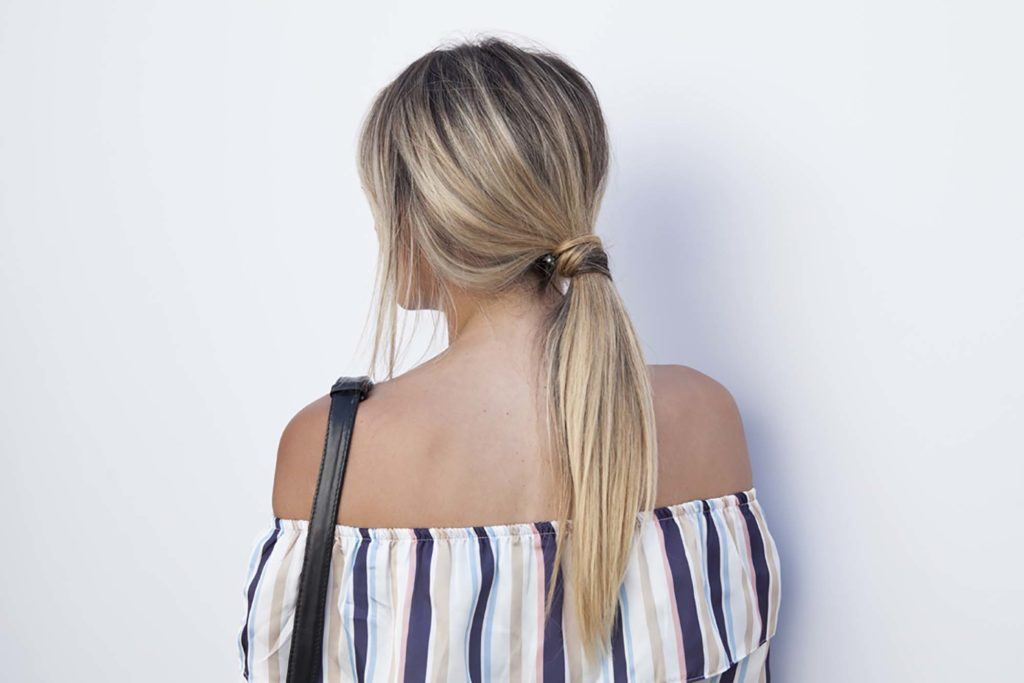 The back view of a blonde woman with a messy long ponytail with an off-the-shoulder striped top