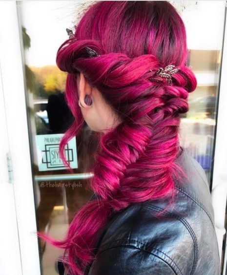 back view of a woman with magenta hair in a fishtail braid