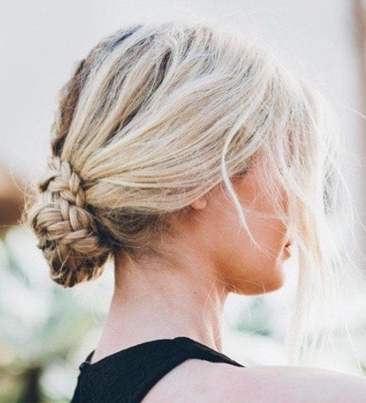 back view of a woman with blonde hair and a low braided bun