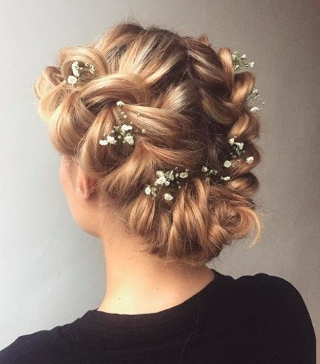 back view image of a woman with blonde hair and a bridal crown braid with fresh flowers