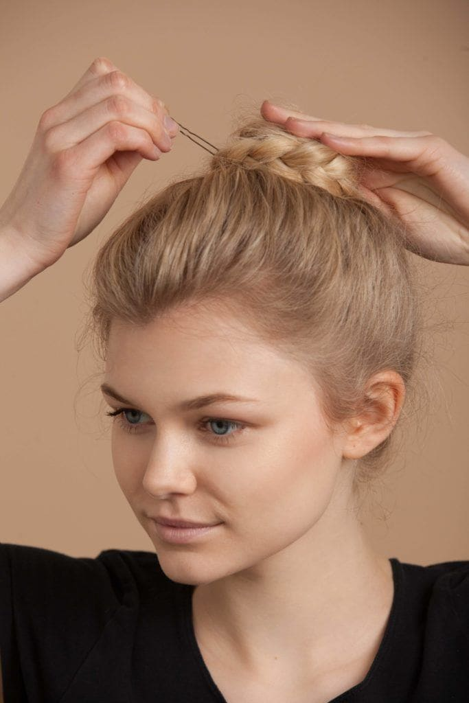 Young blonde woman pinning her quick and easy braided bun hairstyle