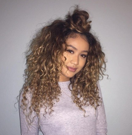 woman wearing grey long sleeved tshirt with her curly ombre hair in a half up bun