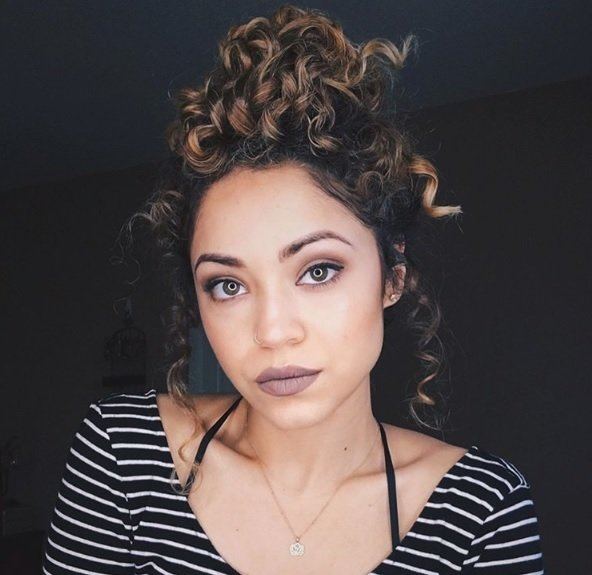 Long curly hairstyles: woman wearing a striped top with her curly brunette hair in a messy bun