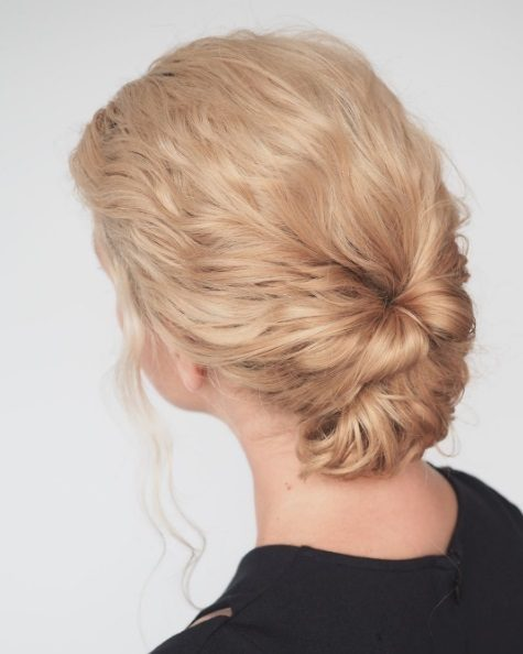 Cute hairstyles for curly hair: blonde woman with curly hair styled into a low chignon