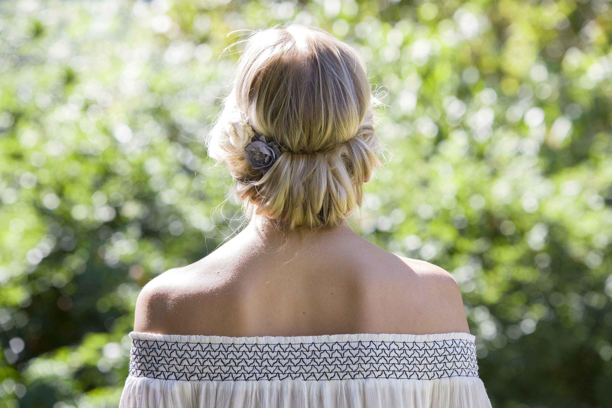 Easy hairstyles for long hair: The back view of a young blonde woman with a headband chignnon AKA cheater's chignon