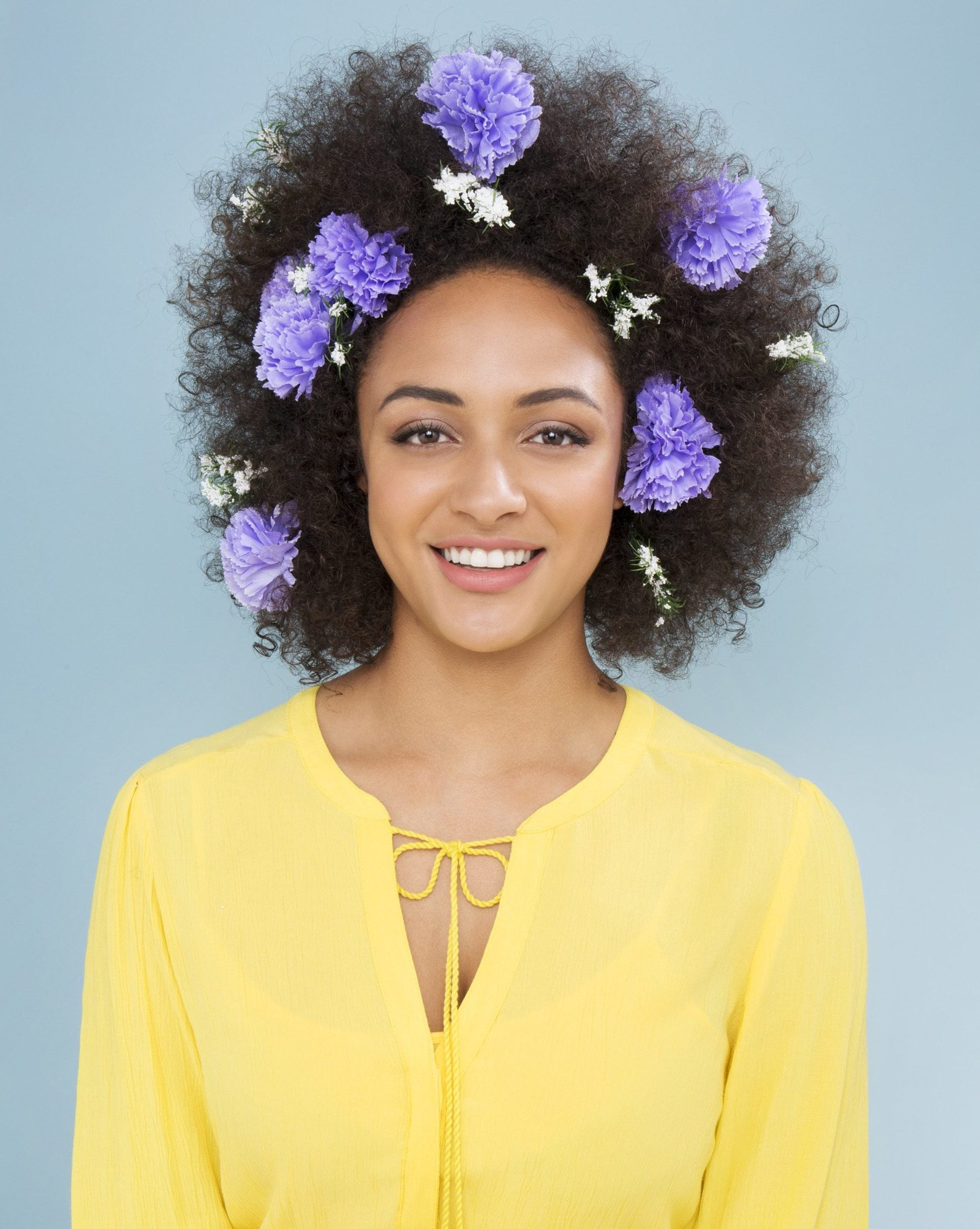 woman wearing a yellow blouse with lilac and white flower hair accessories in her afro