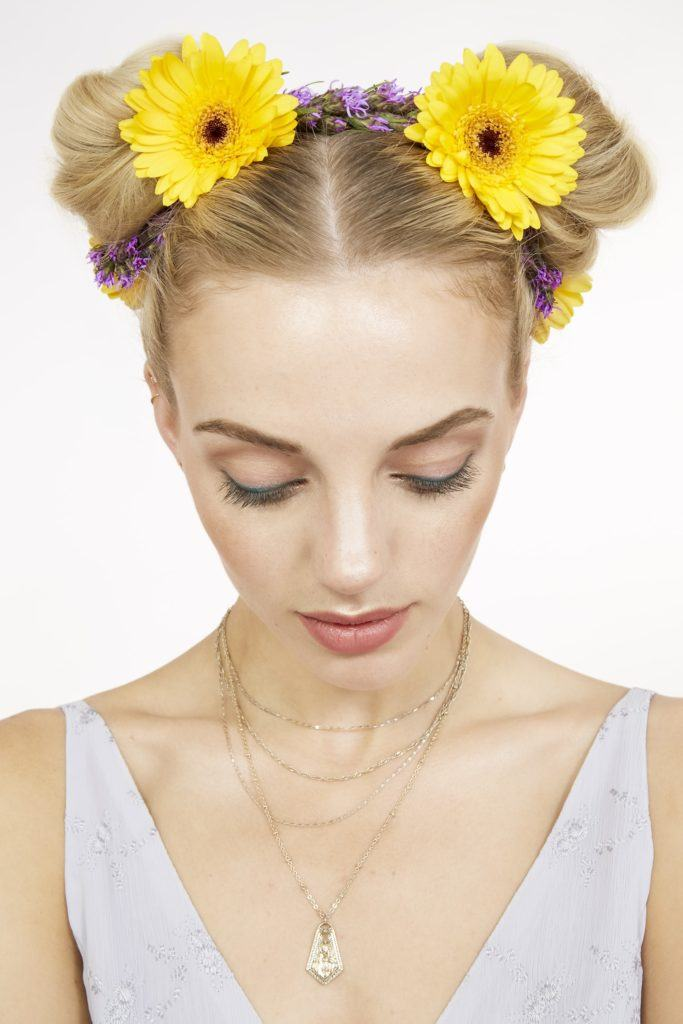 close up shot of blonde model with flowers in her space buns