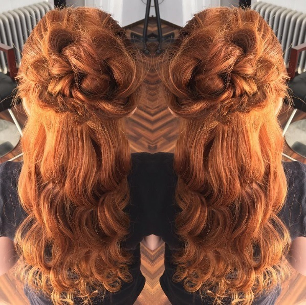 woman with long curly ginger hair with a flower bun