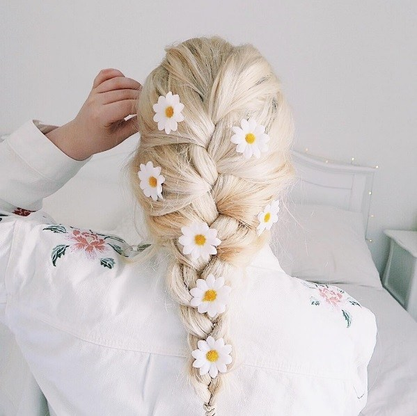 blonde woman with her hair in a french braid with daisy hair accessories