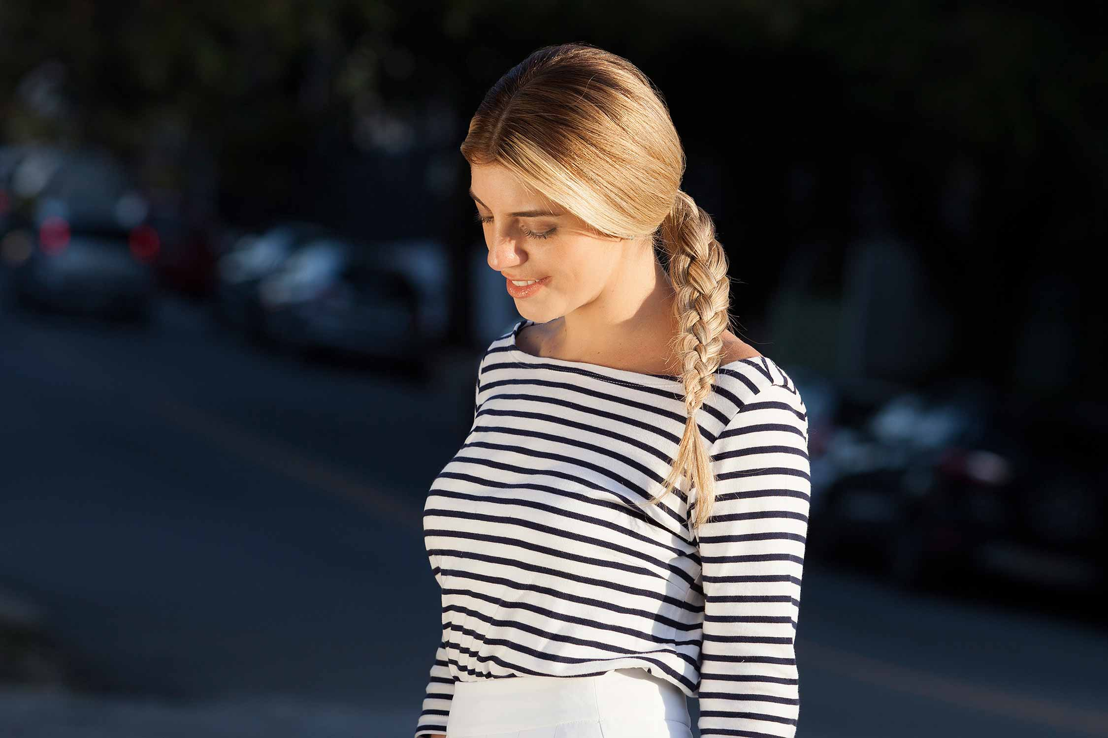 How to do a four strand braid: A blonde woman looking down with a four strand braid, wearing a stripy top and smiling