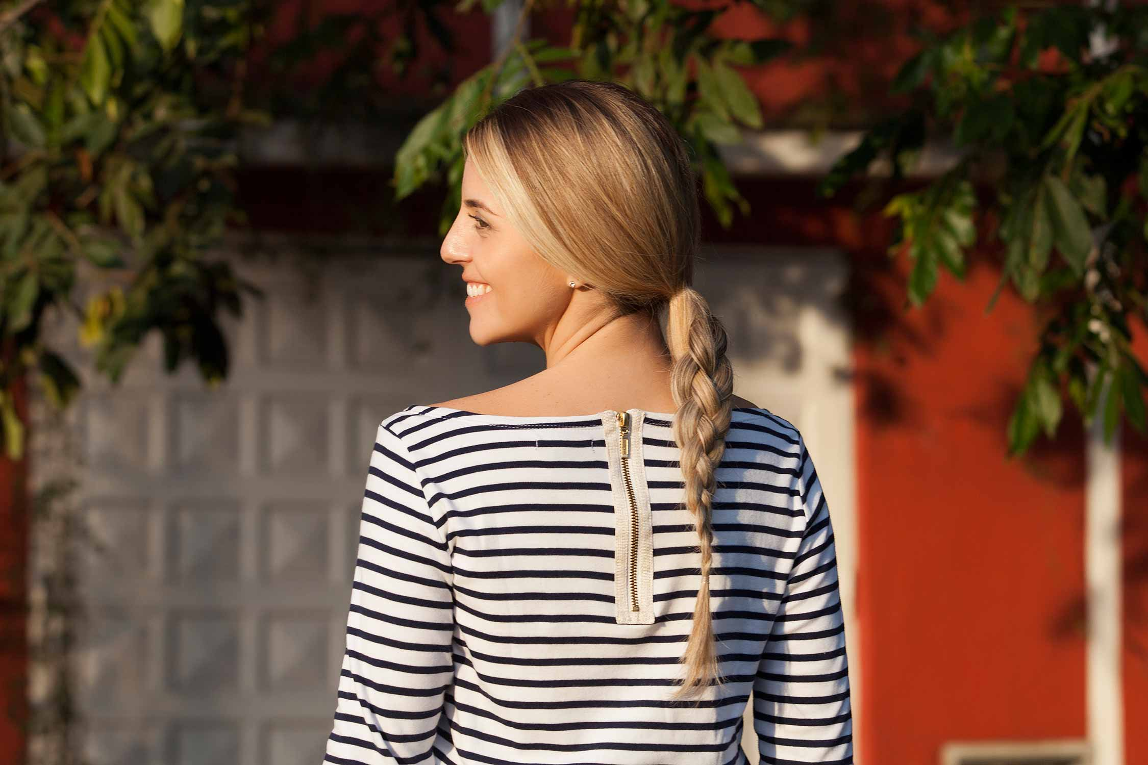 How to braid with four strands: A back view of a blonde woman with a four strand braid, wearing a stripy top and smiling