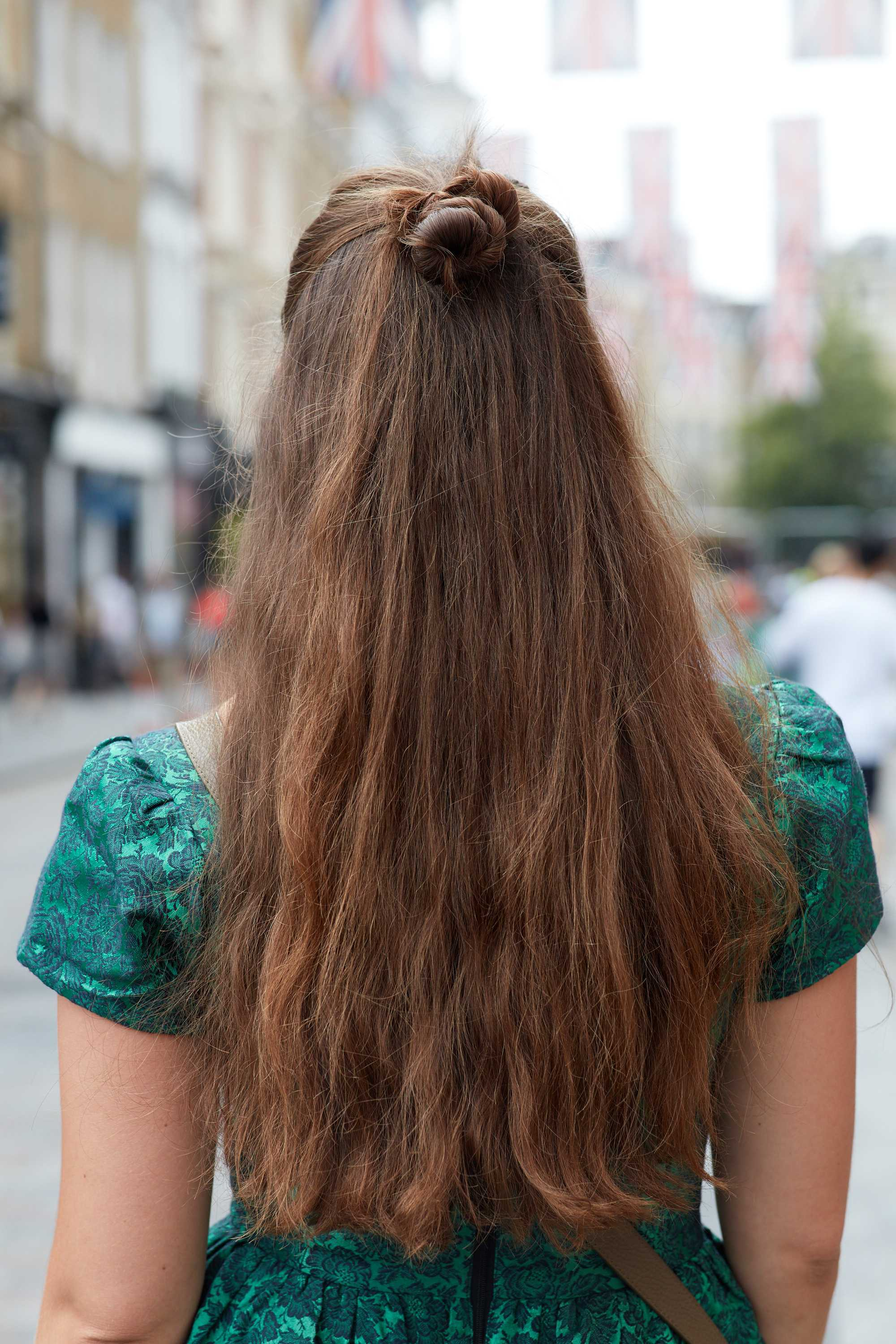 Long hair ideas: Shot of a woman with long chocolate brown hair styled into a half-up, half-down knot bun, wearing green dress and posing outside