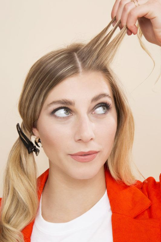 blonde model holding three pieces of her hair up