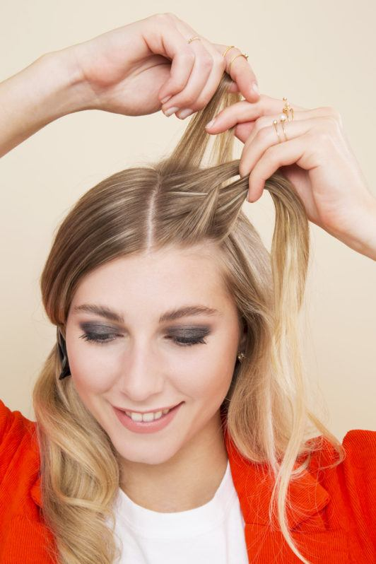 blonde model french braiding half of her hair