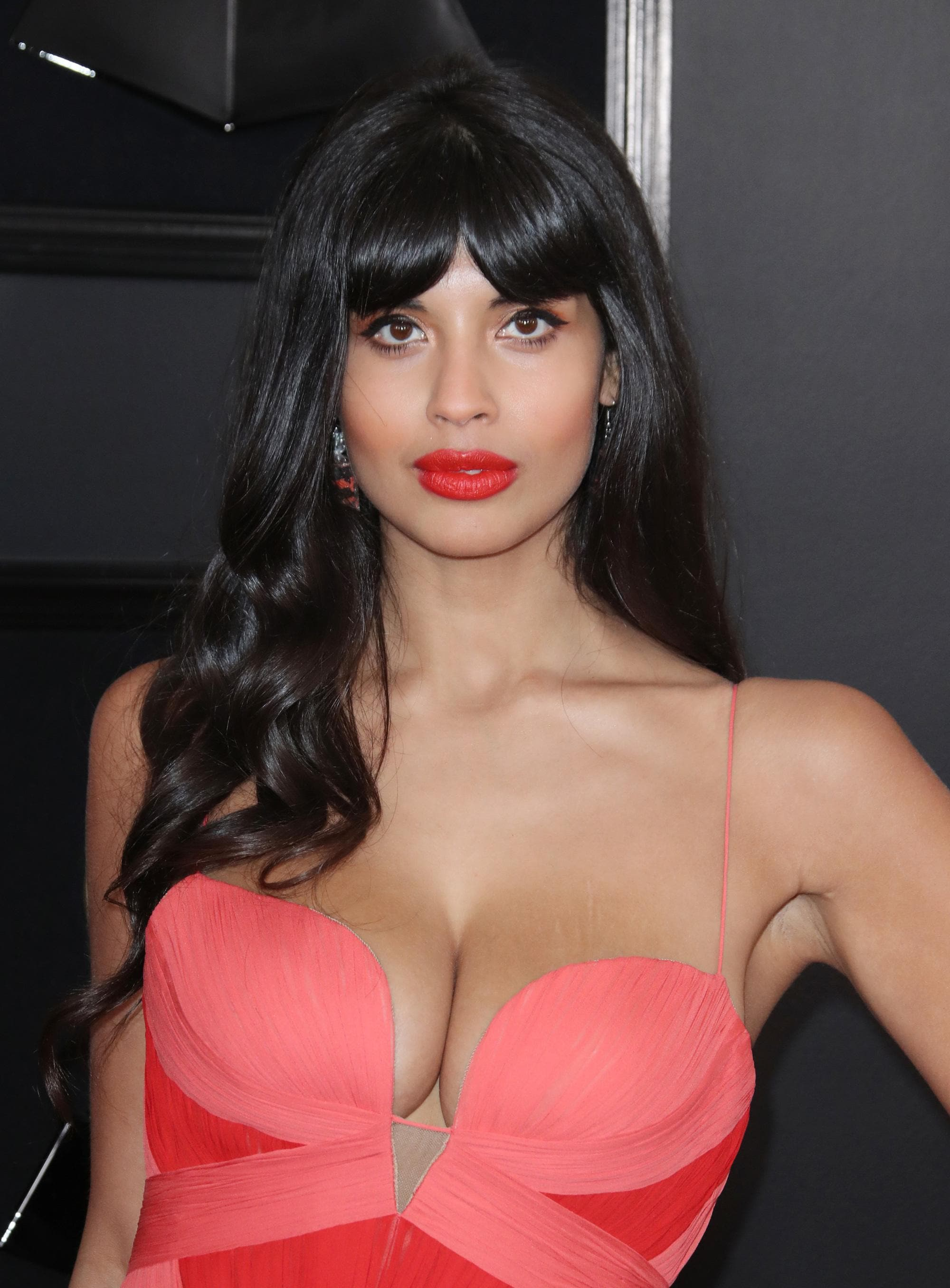 Jameela Jamil with long wavy black hair with '70s style bangs haircut, wearing a red dress with matching lipstick on the red carpet