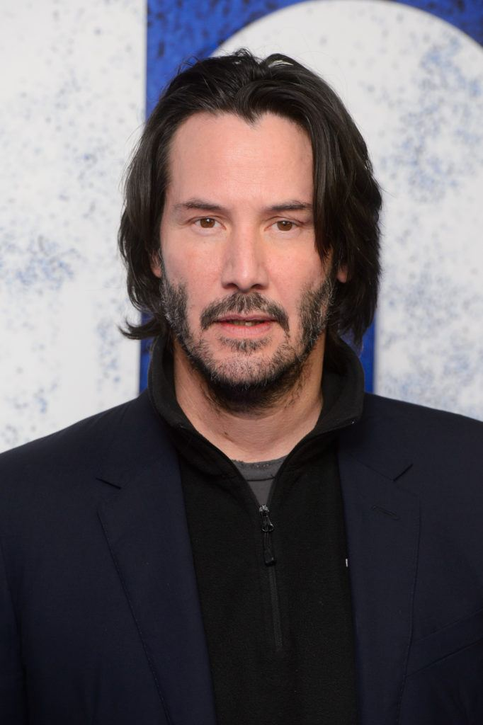 Keanu Reeves On The Red Carpet Wearing A Navy Blue Outfit With His Long Dark Hair