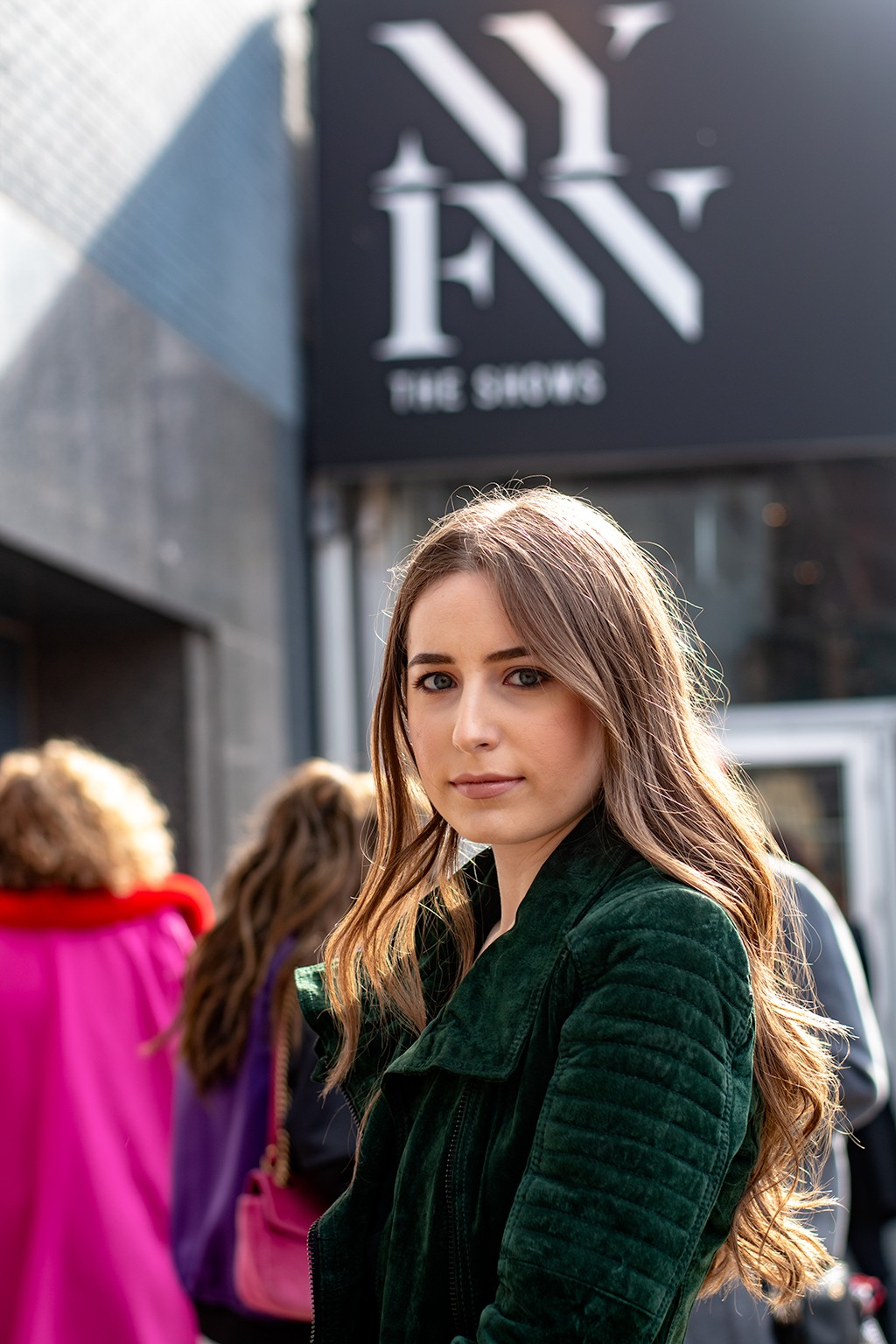 Hairstyle ideas for long hair: Shot of woman with long, loose honey brown waves wearing an emerald green jumper at NYFW