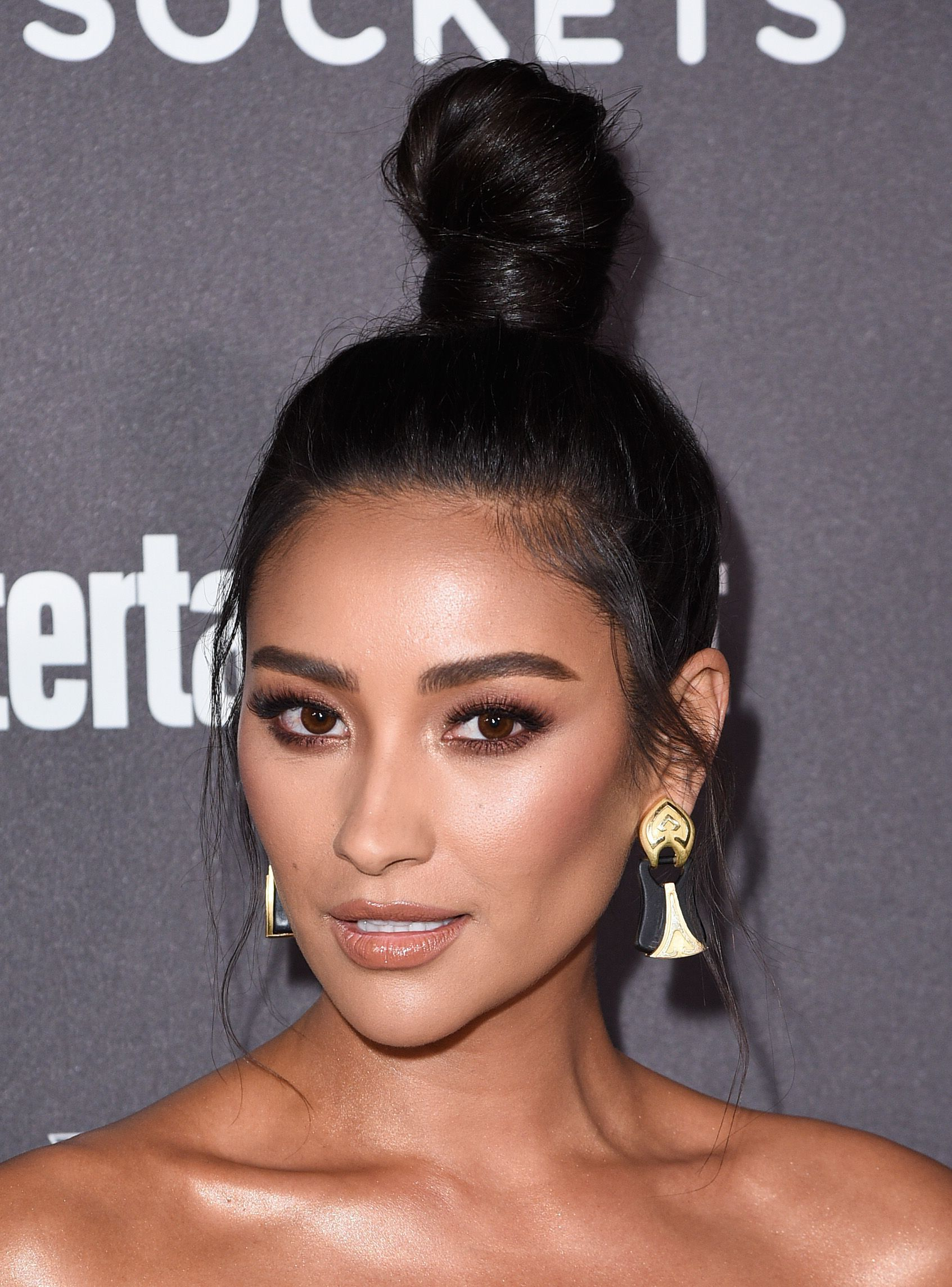 Shay Mitchell with her long dark brown hair styled into a topknot