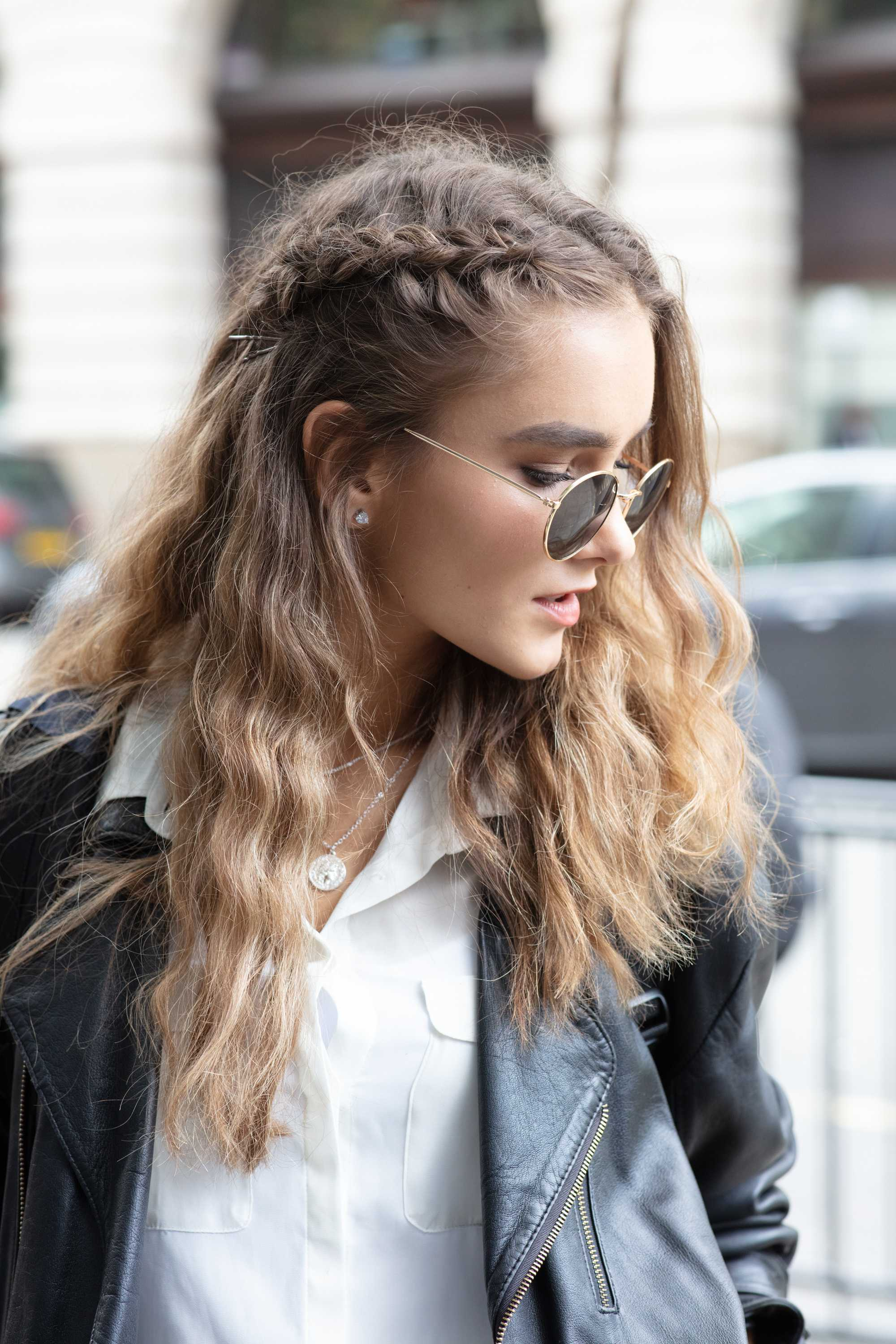 Long hair ideas: Shot of woman with long wavy light brown hair with a side braid, wearing sunglasses and black jacket at LFW
