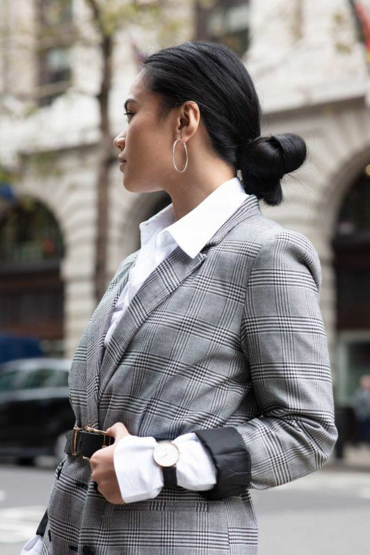 Shot of a woman with long hair styled into a low knot bun, wearing a blazer and posing outside