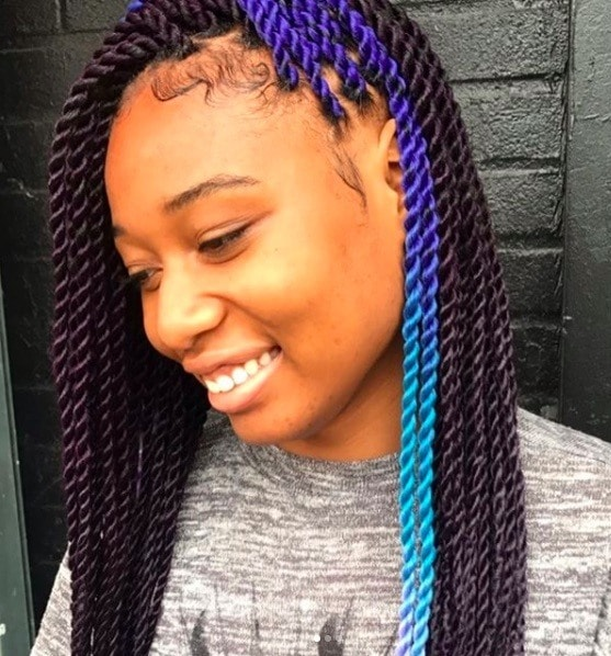 side view of a woman with marley twists and a flash of blue colour in her hair