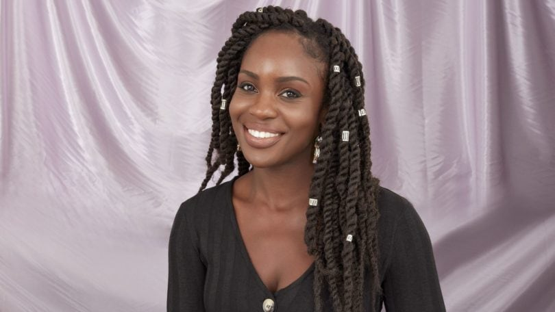 Close up of woman with dark brown marley braid wearing a black button down dress in the in the All Things Hair UK Studio