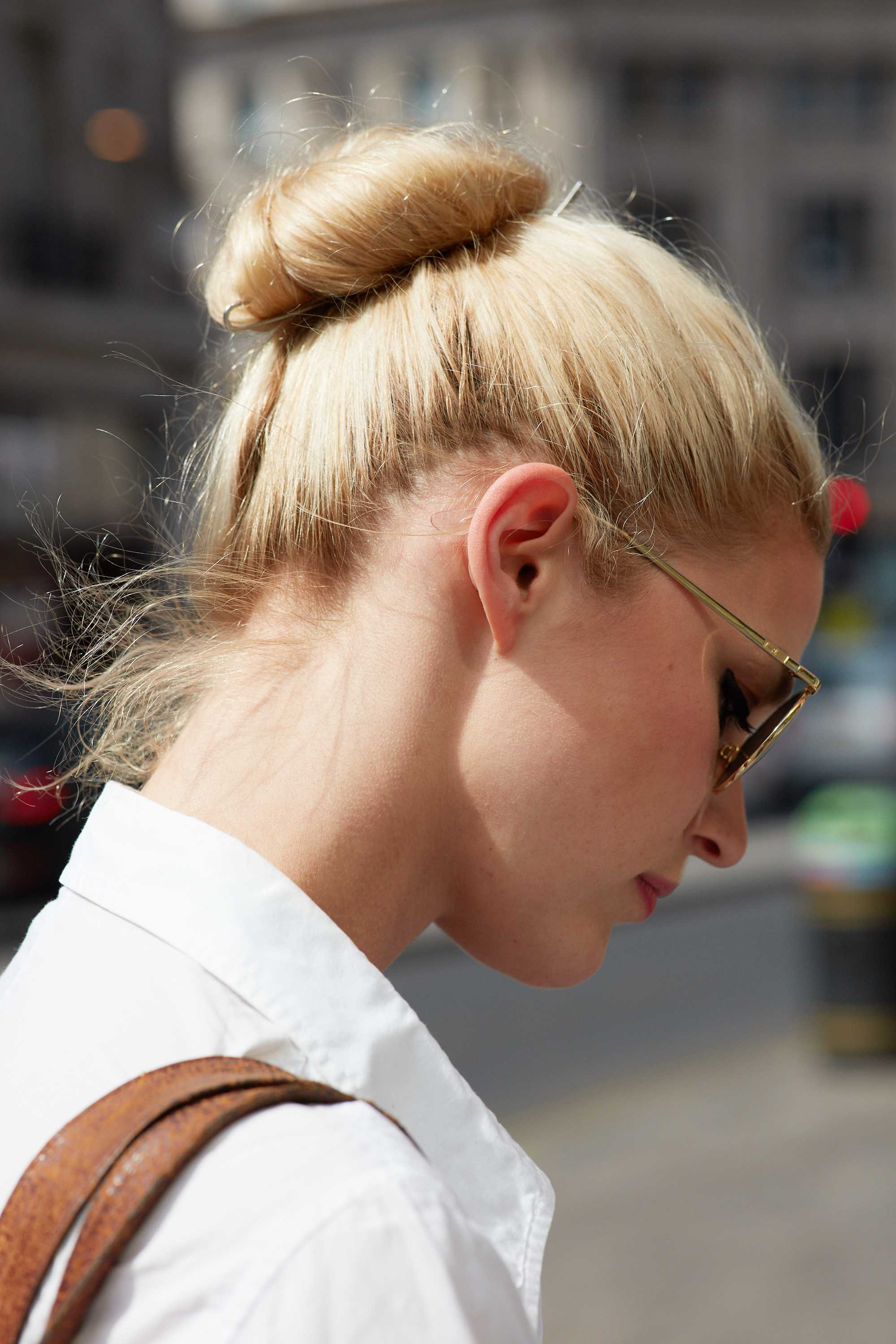 Long hair ideas: Shot of a model with long golden blonde hair styled into a updo hair, wearing a white shirt posing outside