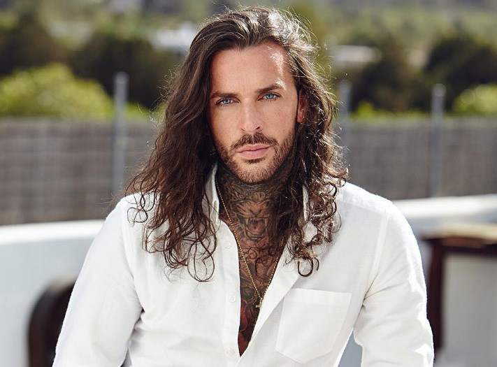 The Only Way Is Essex star Pete Wicks wearing a white shirt with his long hair worn loose and in waves