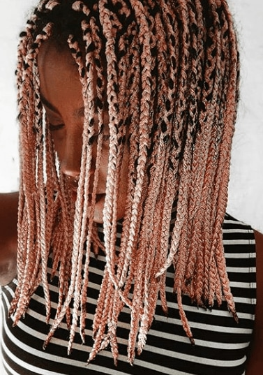pink coloured braids: close up shot of woman with pink box braids, wearing a stripe top and posing against a white setting