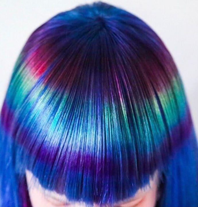 close up of model with prismatic reflection hair designs on her blue denim hair