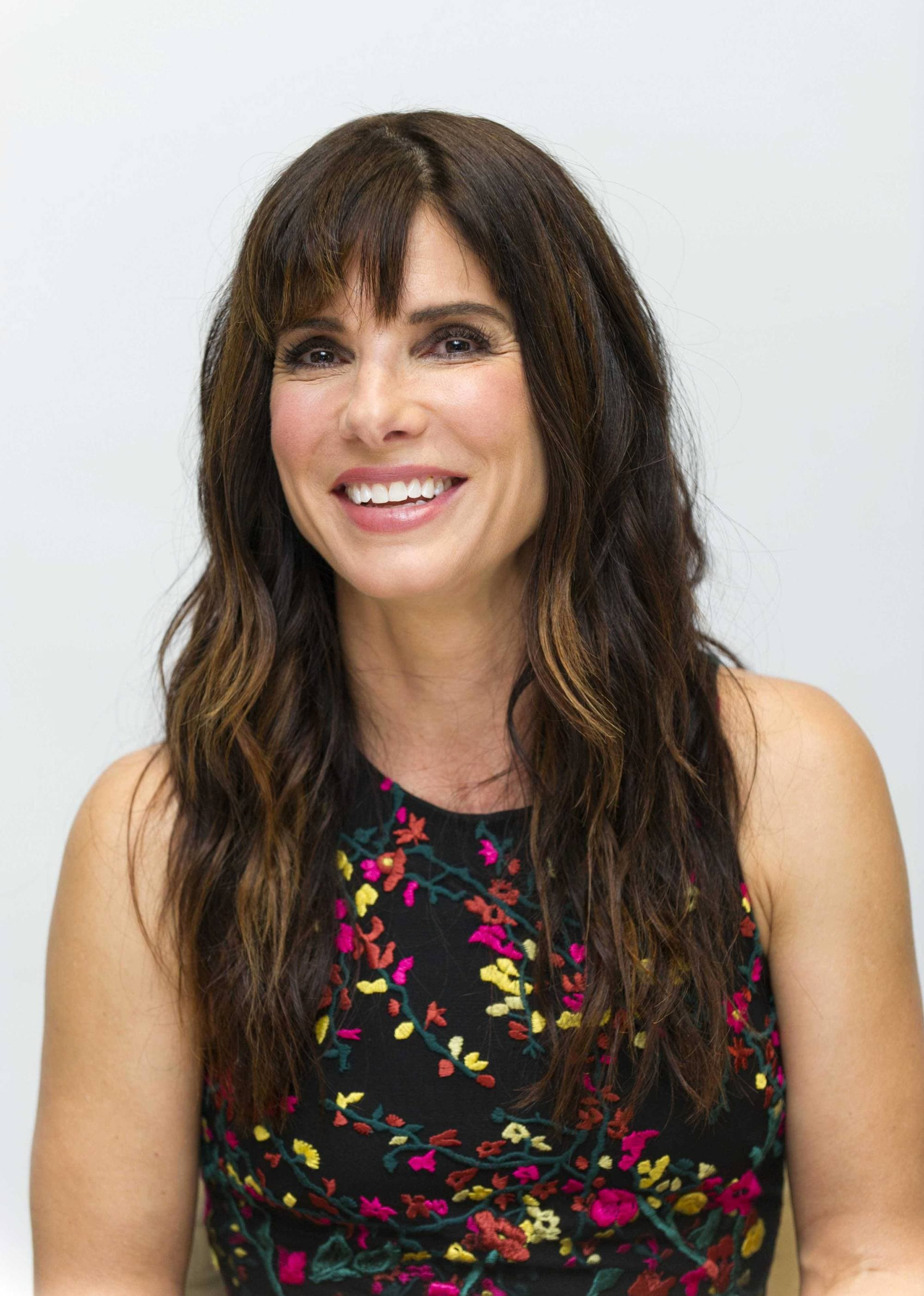 Sandra Bullock with long wavy brown hair and a fringe