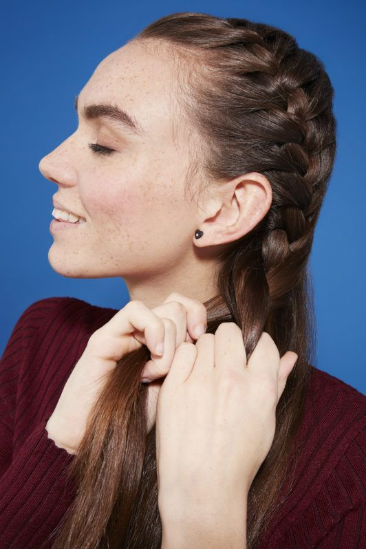 Side French braid how-to: Brunette model braiding her hair into a side French braid, wearing a burgundy knitted jumper