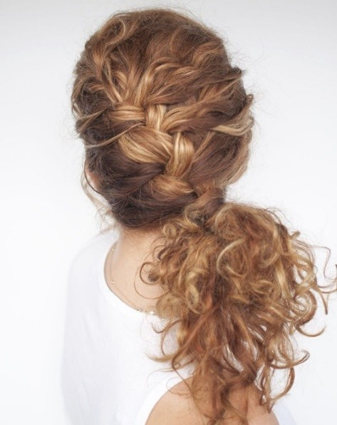 woman wearing a white vest top with her long curly hair in a side french braid
