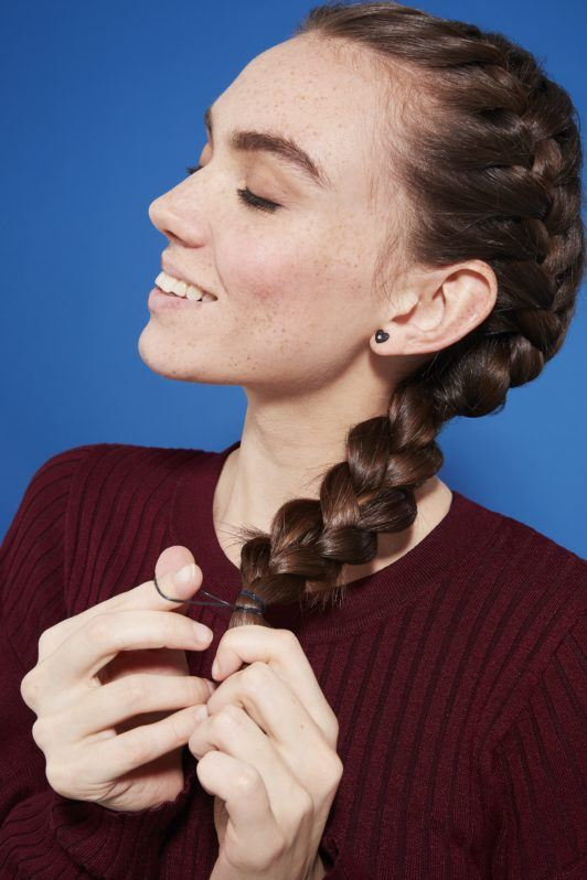 Side French braid how-to: Brunette woman with long hair in a side French braid, tying the bottom with a hair elastic, wearing a burgundy jumper